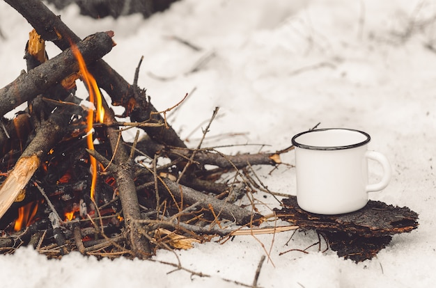 Walking mug with coffee near the campfire.