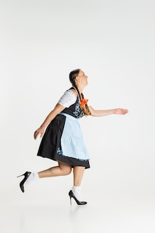 Walking. portrait of beautiful woman, waitress in traditional austrian or bavarian costume standing alone isolated over white background. holiday event, celebration, oktoberfest, festival concept.