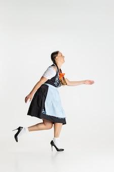 걷는. 아름다운 여성의 초상화, 전통적인 오스트리아 또는 바이에른 의상을 입은 웨이트리스가 흰색 배경에 고립되어 있습니다. 휴일 이벤트, 축하, 옥토버페스트, 축제 개념.