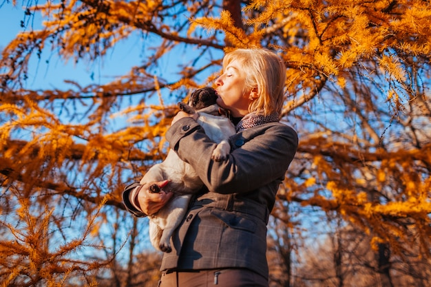 Walking pug dog in autumn park. happy woman hugging and kissing pet .