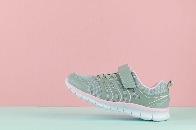 Walking sneaker with left foot on blue and pink background.