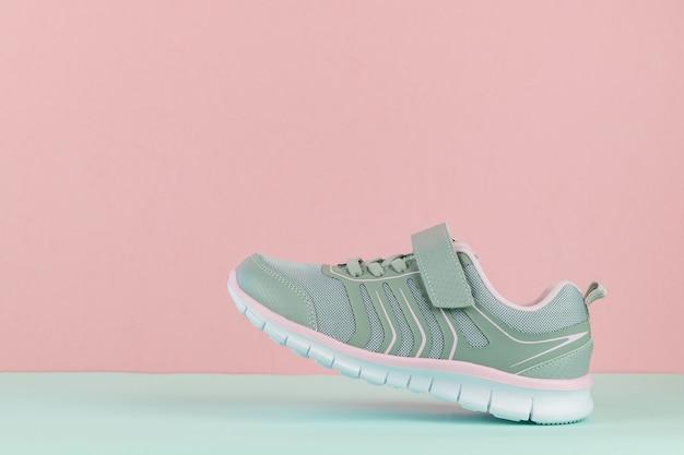 Кроссовки для ходьбы с левой ногой на синем и розовом фоне.