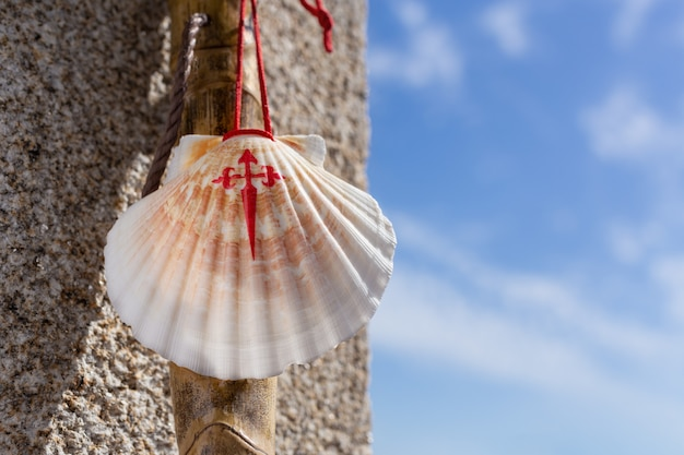Walking stick and seashell of the camino de santiago leaning on granite stone wall. santiago de compostela pilgrimage concept