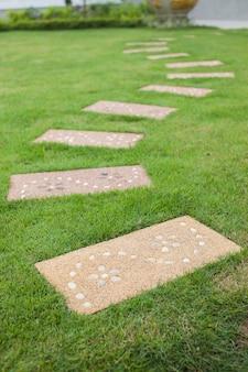 Прогулочный камень по траве.