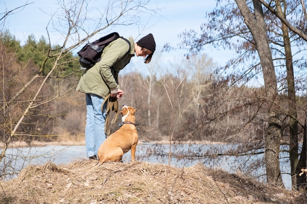 Walking and teaching dog in the wild. woman communicating with her dog at the forest by the river, casual and hiking style