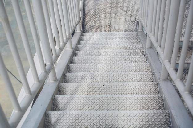 계단을 걷는 흰색 저장 탱크 화학 물질.