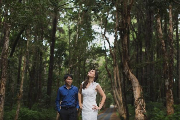 숲에서 젊은 신부와 신랑 산책