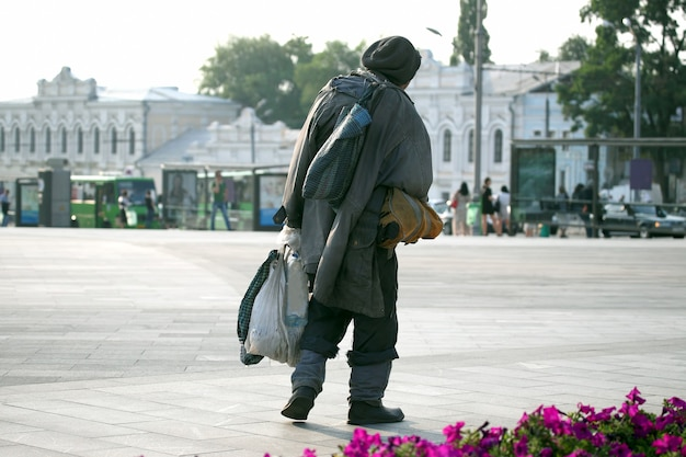 町の広場を歩くホームレスの男性