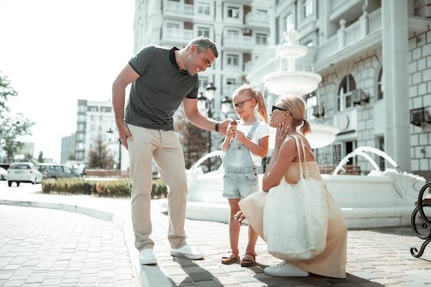 一緒に歩きます。街の通りを歩いているときに彼女を見ている陽気な両親と話している彼女の手にアイスクリームコーンを持った笑顔の少女。