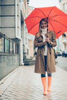 Прогулка с зонтиком. полная длина привлекательной молодой улыбающейся женщины в красочных резиновых сапогах с зонтиком и смотрящей в камеру во время прогулки по улице