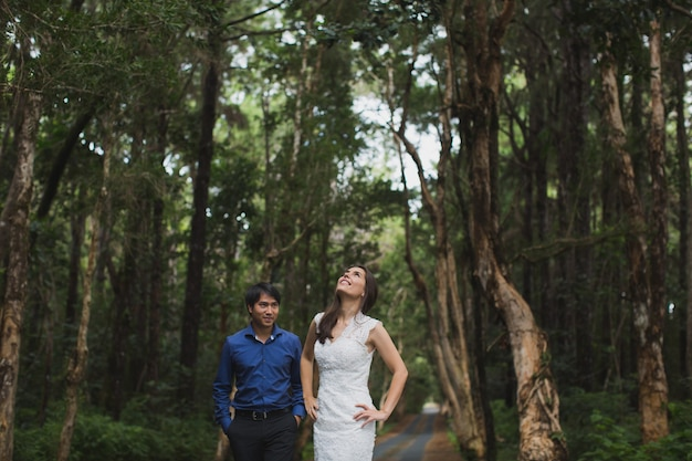 Walking the young bride and groom in the forest