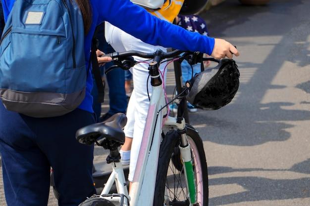 自転車で歩くバックパックとヘルメットを持ったサイクリストが自転車をリードするサイクリングのコンセプト