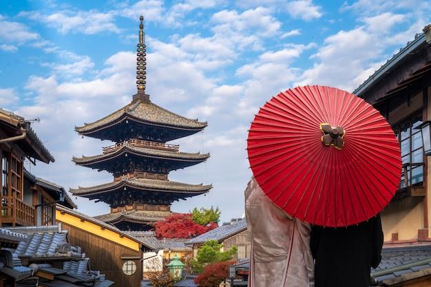 京都の伝統的な家と八坂の塔の背景を持つ古い市場の通路