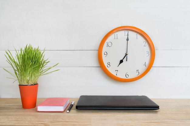 Wall clock, laptop, notebook and pen. home workplace. green houseplant on the table.