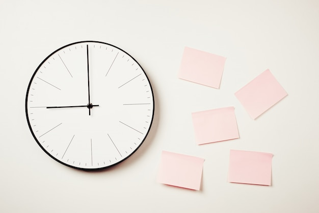 Wall clock and pink stickers on a white background.