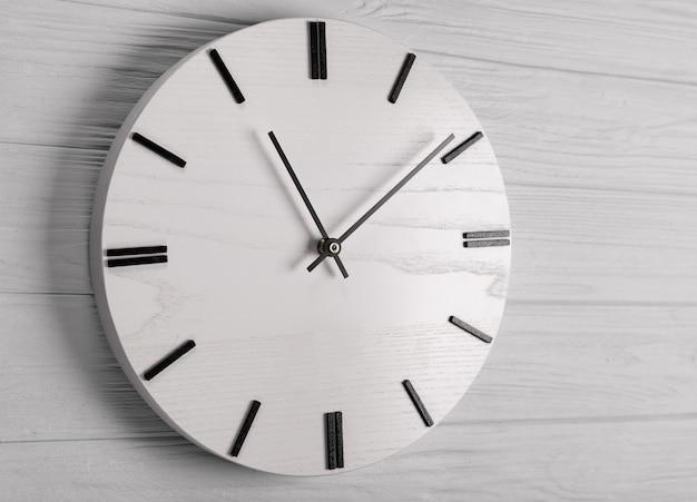 Wall clock at wooden wall