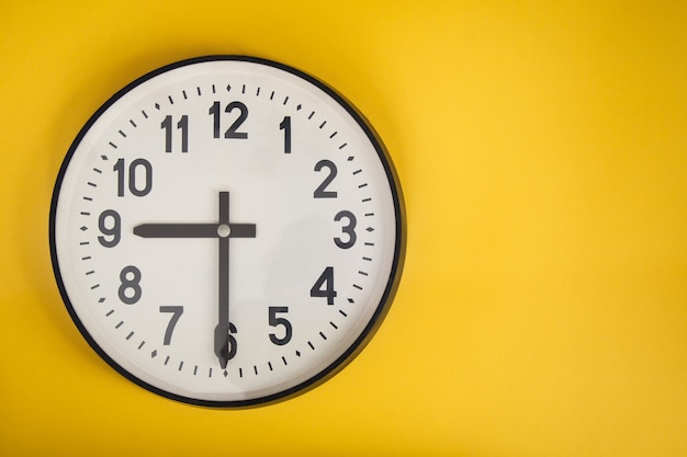 Wall clock on yellow wall. copyspace