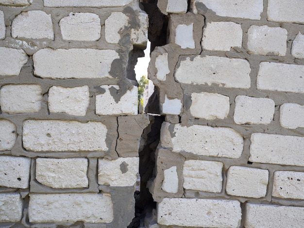 A wall of concrete blocks with a huge crack