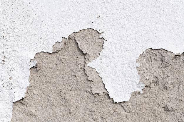 屋外での壁の損傷。石膏とペイントの詰まり、表面の損傷。皮をむいた漆喰壁の背景