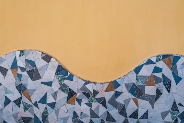 깨진 타일 모자이크라고도 알려진 trencadis의 장식용 파도로 장식 된 벽