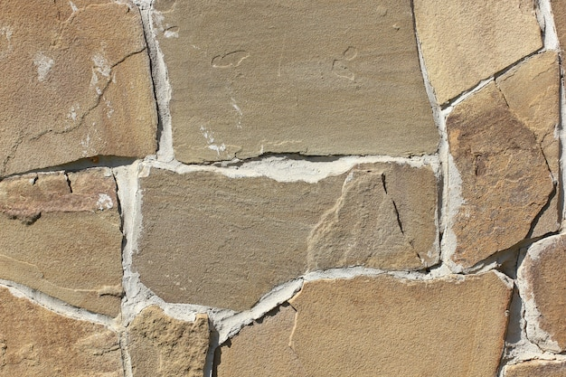 Wall finished with stone sandstone of irregular shape on cement mortar