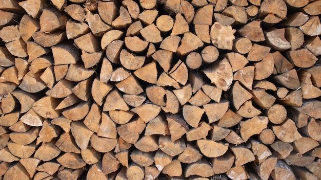 壁の薪、山積みの乾燥したみじん切りの薪の背景。