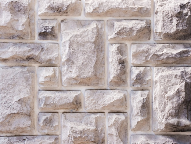 A wall from an artificial gray stone facade with rough fractured surfaces