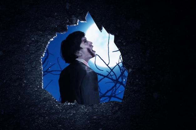夜景を背景に立っている怖いゾンビの壁の穴