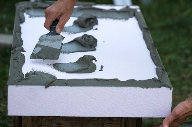 ポリスチレンパネルの壁断熱材、接着剤の塗布と設置。