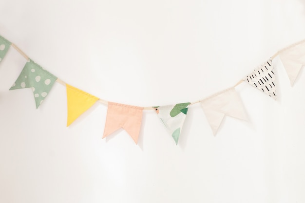 Wall is decorated with multi-colored flags for children. birthday decor decoration flags.