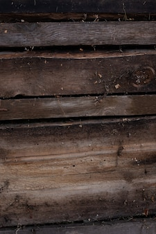 Wall is made of dirty old boards background is made of dark brown wood covered with dust and cobwebs...