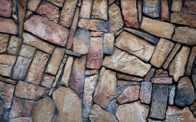 The wall is made of multicolored natural stone the masonry is stone on cement stone wall