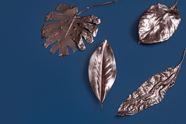 The wall is painted with leaves of gold color on a blue wall .
