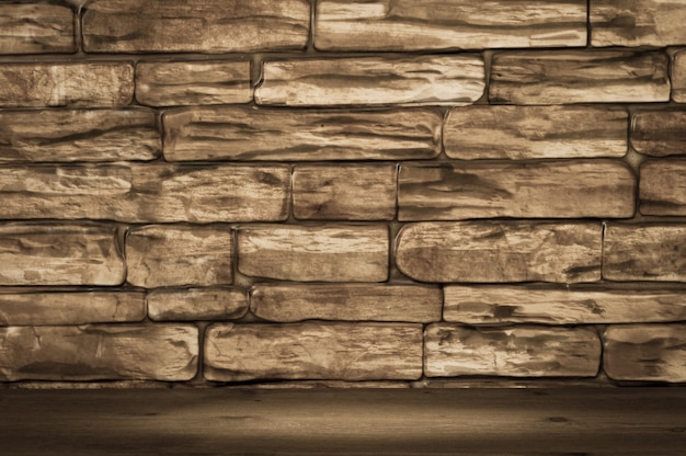 Wall of large brown bricks and wooden boards with spot lighting.