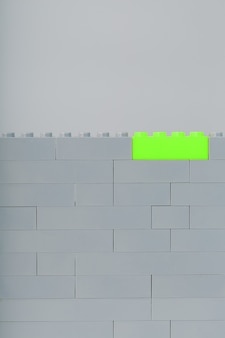 A wall made of children's construction kit parts with bright green bricks
