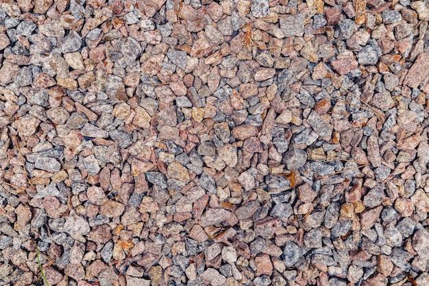 Wall of natural grey granite crushed stone, macadam.