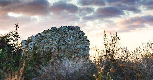 日没時の暗い雲を背景にした廃墟の家の壁_