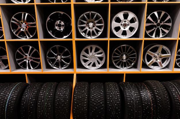 상점에있는 합금 자동차 바퀴와 공기 타이어의 벽. 계절 휠 저장