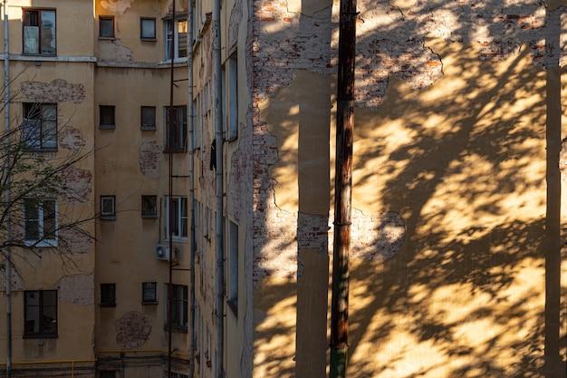 さびた排水管と木からの対照的な影のある崩れかけた漆喰のある古い高層ビルの壁