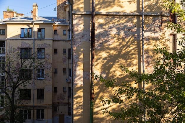 木からの対照的な影と崩れかけた漆喰の古い高層ビルの壁