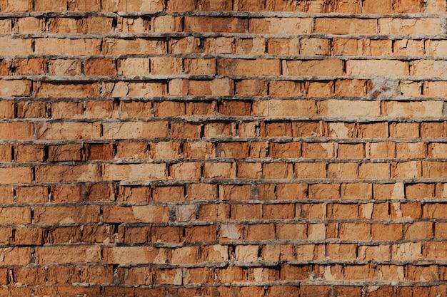 오래 된 주황색 점토 벽돌의 벽은 빈티지 돌 배경을 망쳤습니다. 거친 세 벽돌 배경 표면 o...