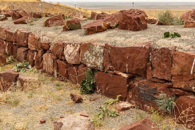 赤い石の壁、アクルタス宮殿の複合体の古代の壁を台無しにしました。カザフスタン