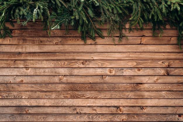 나무 울타리의 벽입니다. 겨울 나무 판자 배경, 갈색 수평 보드, 나무 질감, 울타리 및 전나무 브런치. 스톡 사진