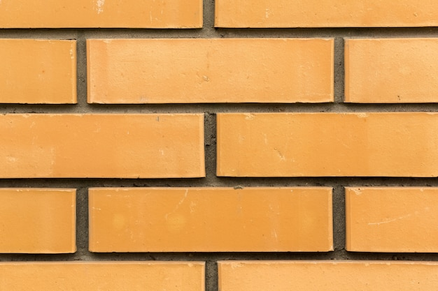 セメントの継ぎ目が付いている黄色いレンガの壁