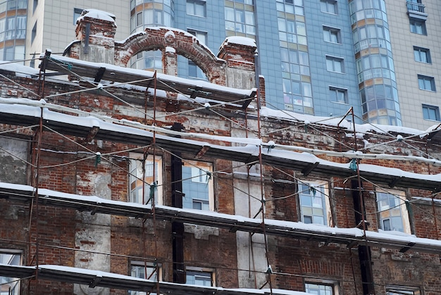 Wall of an old building in scaffolding against the background of a modern multistorey building