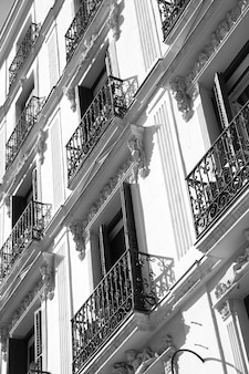 Wall of old building with small balconies in madrid, spain. black and white image