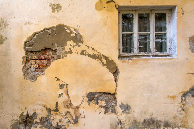The wall of an old house with a window. the wall needs repair, collapsed plaster and brickwork.
