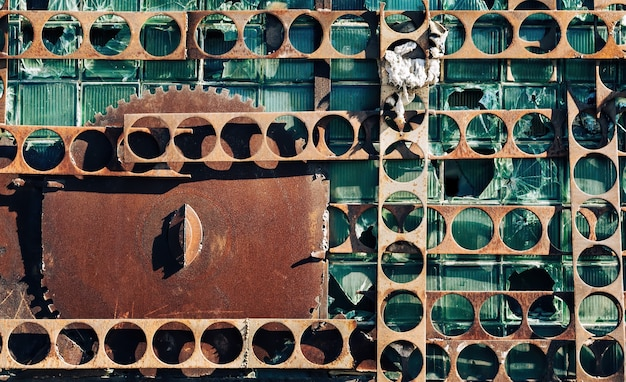 Wall of an old industrial building with broken glass panels and rusty metal plates. abstract background