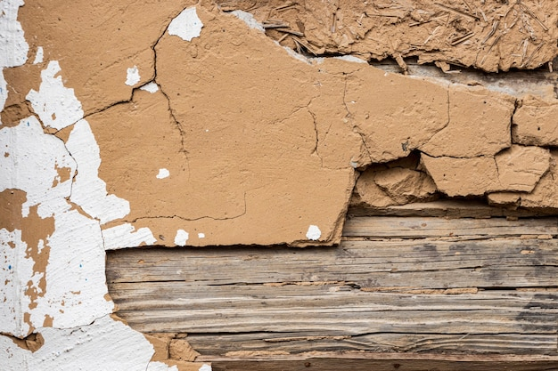 Wall of an old log house. clay and wood. wooden slats. old stucco. grunge background and texture. concept for design and interior.