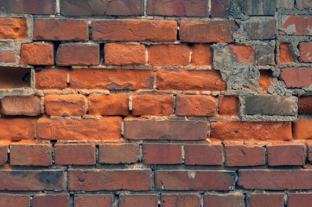 Wall of old red clay bricks ruined vintage stone background rough aged masonry backdrop surface of grunge brick texture for design and decoration loft style for exterior and interior decoration